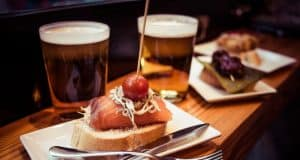 Tapas gratis con cañas de cerveza en barra de bar