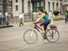 Ciclista por calle Alcalá, Madrid y peatones por detrás
