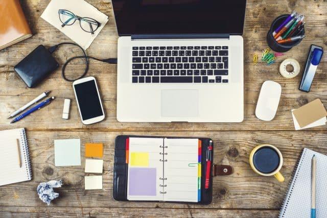 Mesa de trabajo con ordenador, agenda, móvil, posits,...