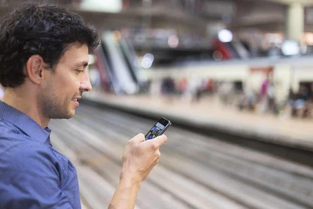 Hombre mirando su móvil en metro de madrid, consulta de app transporte público