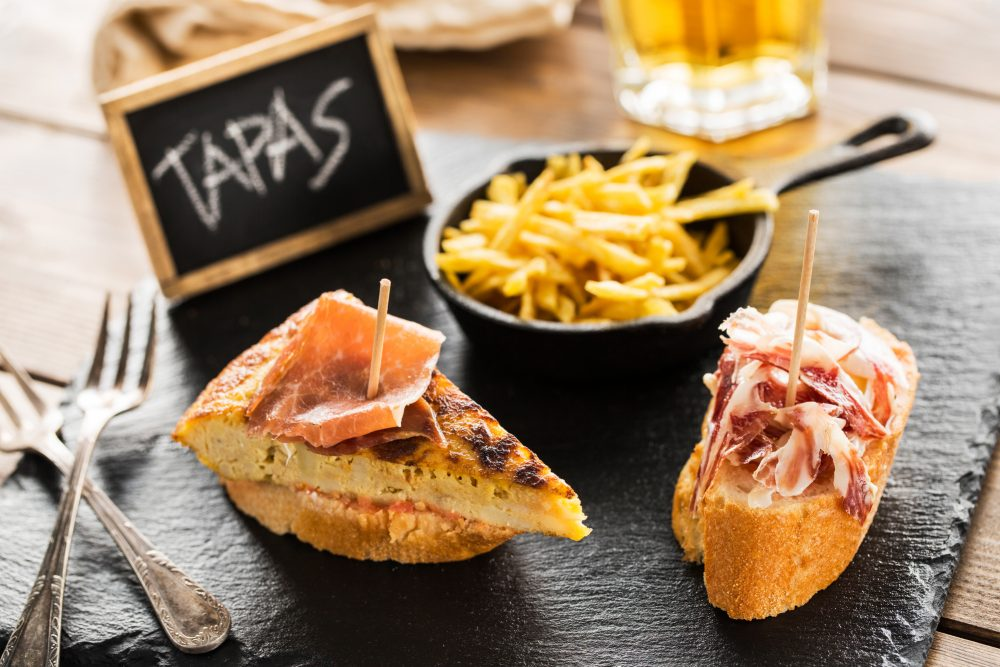 Pinchos de tortilla con cartel de Tapas en un bar